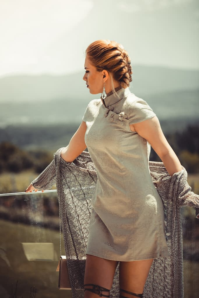 Dating Tips: Woman with brownish-red braided hair, wearing a tan colored dress and light colored sweater around her arms