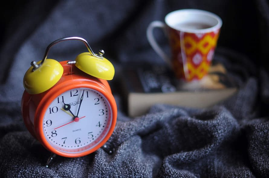 Red-Orange clock with yellow bells, a book and a red and yellow cup, laying on top of a navy blanket