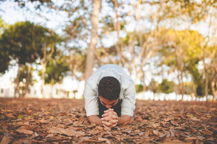 Man who wants to date, praying for forgiveness of self in a park