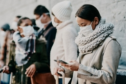 woman wearing a face mask, scarf and a warm tan jacket attempting to online date during the COVID-19 pandemic