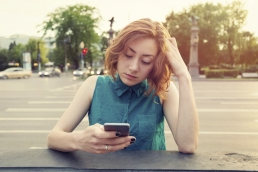 Caucasian woman with red hair, sitting on a street corner look at her online dating app on her cell phone frustrated