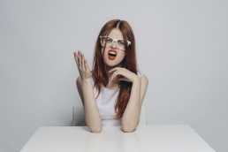 Caucasian woman with white glasses and red hair, sad and worried about ghosting from the men she's meeting online