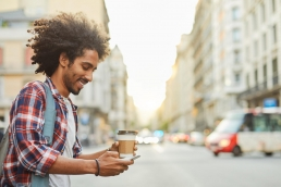 You African American man with curly hair, holding a coffee, in a textationship on the the go, messaging a woman with a woman