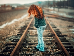 Red Haired Woman sad about her relationships, standing on the train tracks because the pain of her relationships are unbearable