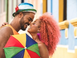 Teen male with hat and beard, celebrating a date a Carnival with a female with orange curly hair and a multicolored umbrella