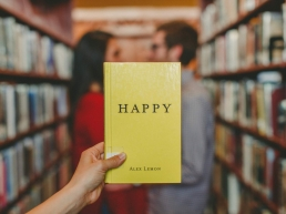 Happiness image of a man and woman in a library aisle facing each other. Another person whose arm is visible, is holding a yellow book titled,