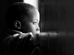 African American boy staring out of a window