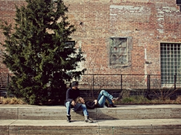 Man and woman sitting on the side of a building spending intimate time without sexual foreplay