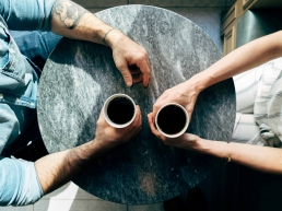 Man and woman sitting at a table on a date drinking coffee and asking each other questions