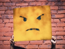 Demon poster of an angry face against a brick wall