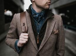 Alpha male wearing a brown blazer, and satchel walking down a corridor