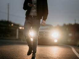 man walking on a road looking at his cell phone distracted with a car approaching from behind