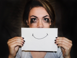 Woman holding a drawing of a smile over her face