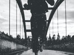 woman running on a bridge in the rain