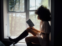 tough girls: African American woman with an afro in a window reading a book.