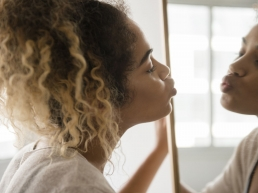 African American woman with curly hair promoting self-love by kissing herself in a mirror