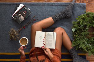 tough girls: woman laying on the couch drinking coffee while reading a book